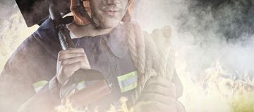 Composite image of professional fireman. Professional Fireman against grey room Royalty Free Stock Photo