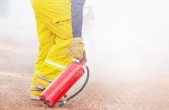 Professional fireman in yellow fire fighter uniform holding extinguisher fighting fire royalty free stock photography