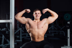 Professional fitness bodybuilder sitting on the bench and demonstrates muscles of your body after a workout, at gym. Stock Photo