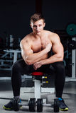 Professional fitness bodybuilder sitting on the bench and demonstrates muscles of your body after a workout, at gym. Big Confident muscular man training Royalty Free Stock Photos