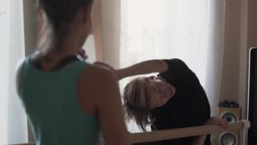 Professional flexible female trainer showing to the girl how to stretch her legs. Fitness trainer working with the young. Professional female trainer showing to stock video