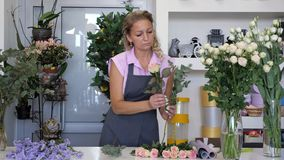 Woman florist makes bouquet from pink roses, blue gypsophila and green leaves.
