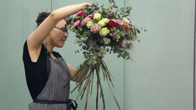 Professional flower arranger shows how to make a mixed flower bouquet stock footage