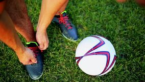 Professional football player at practice tying laces in the boots. Close-up with the ball. Professional football player at practice tying laces in the boots stock video