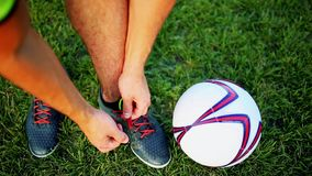 Professional football player at practice tying laces in the boots. Close-up with the ball. Professional football player at practice tying laces in the boots stock footage