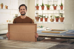 Professional framer in his studio workshop smiling. Portrait of a young male professional framer holding a newly framed work while smiling confidently at the Royalty Free Stock Image