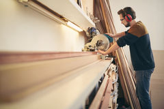 Professional framer using a work tool to saw through wood. Professional craftsman at work in a framing workshop using a saw tool to work with wood Royalty Free Stock Image