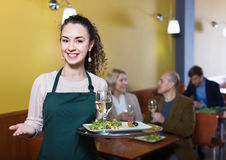 Professional friendly smiling nippy with tray posing. At table of senior customers Stock Image