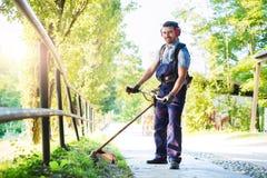 Professional gardener mowing grass in home garden Stock Photos