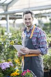 Professional gardener using a digital tablet in a garden center.  Stock Images