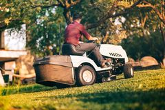 Professional gardner worker using lawn mower for cutting grass in garden. Professional worker using lawn mower for cutting grass in garden Royalty Free Stock Photos