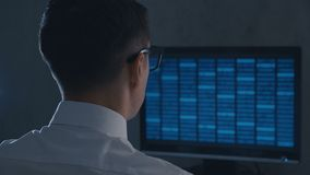 Professional IT geek programmer in glasses is working on computer with binary code at night office stock footage