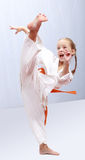 Professional girl does karate kick royalty free stock photography