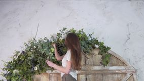 Professional girl florist with eucalyptus branches in her hands decorates flowers on the beautiful wooden gate royalty free stock photos