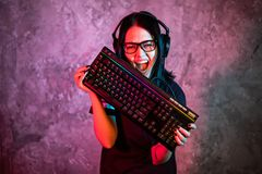 Professional Girl Gamer in MMORPG Strategy Video Game. She`s She posing over colorful blue and pink background with a. Gaming keyboard. She Wears Gaming Headset stock image