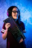 Professional Girl Gamer in MMORPG Strategy Video Game. She`s She posing over colorful blue and pink background with a. Gaming keyboard. She Wears Gaming Headset royalty free stock photo