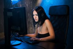 Professional Girl Gamer Plays in MMORPG or Strategy Video Game on Her Computer. She`s Participating in Online Cyber. Games Tournament, Plays at Home, or in royalty free stock image