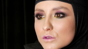 Professional girl model with beautiful makeup poses in a black cap on her head in front of the camera on black stock video footage
