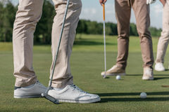 Professional golf players getting ready to shot a ball Royalty Free Stock Photography