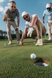 Professional golf players looking at ball near the hole Royalty Free Stock Photos