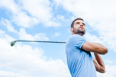 Professional golfer. Low angle view of young and confident golfer swinging his driver and looking away with blue sky as background Stock Photos