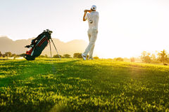 Professional golfer taking shot on golf course royalty free stock photo