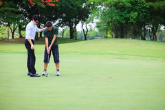 Professional golfer teaching to play golf Stock Photos