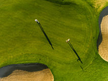 Professional golfers playing on putting green. Aerial view of professional golfers playing on putting green on a summer day. Players on a green golf course stock photo