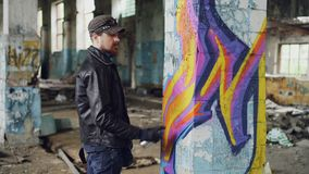 Professional graffiti painter is creating abstract image on large pillar inside abandoned building with spray paint. Young man is wearing leather jacket, jeans stock footage