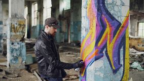 Professional graffiti painter is creating abstract image on large pillar inside abandoned building with spray paint. Young man is wearing leather jacket, jeans stock video