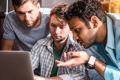 Professional group using laptop and discussing business project together Stock Photos