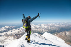 Professional guide Hiker at the top of the rock with his hands up is pleased with the next victory of the ascent. On a sunny afternoon Stock Images