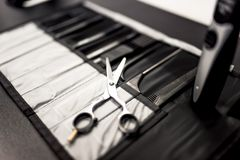 Professional haidresser tools on table with close-up of scissors. And black combs set Royalty Free Stock Image
