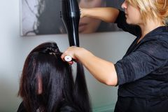 Professional hair stylist with hairdryer and comb working at customer`s hair. Stock Photos
