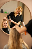 Professional hair stylist at work - hairdresser  doing hairstyle Stock Photos
