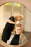 Professional hair stylist at work - hairdresser  doing hairstyle Stock Image