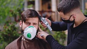 Professional haircut barber man at home in the garden with a protective mask doing a haircut for a guy he using the hair