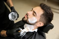 Professional hairdresser applying shaving foam onto client`s skin. In barbershop stock photography