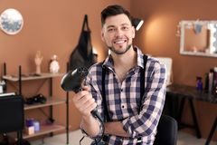 Professional hairdresser with blow dryer. In beauty salon Royalty Free Stock Image