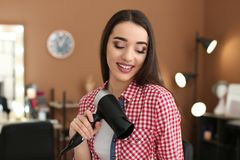 Professional hairdresser with blow dryer. In beauty salon Stock Photo