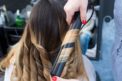 Professional hairdresser curling ombre hair with iron Royalty Free Stock Images