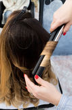Professional hairdresser curling ombre hair with iron Stock Photos