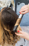 Professional hairdresser curling ombre hair with iron in beauty Stock Photos