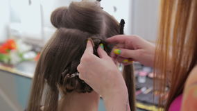 Professional hairdresser doing hairstyle for pretty teen girl stock footage