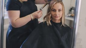 Professional hairdresser doing hairstyle and using straightener on beautiful long blond woman hair in beauty salon stock video