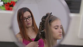 Professional hairdresser doing hairstyle for young pretty woman - making curls stock footage