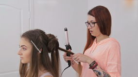 Professional hairdresser doing hairstyle for young pretty woman - making curls stock video footage