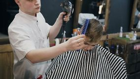 Professional hairdresser drying hair of little boy with hairdryer and brush in barbershop. Wet hair little boy is dried. By hairdryer. Barbershop, slow motion stock video footage