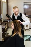 Professional hairdresser drying hair stock images