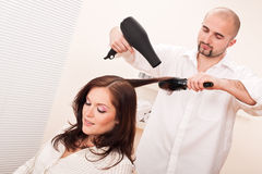Professional hairdresser with hair dryer Stock Images
